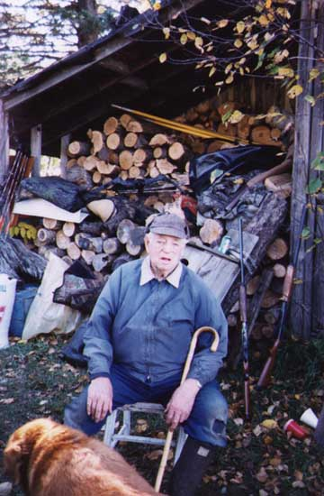 Grandad in front of the firewood supply